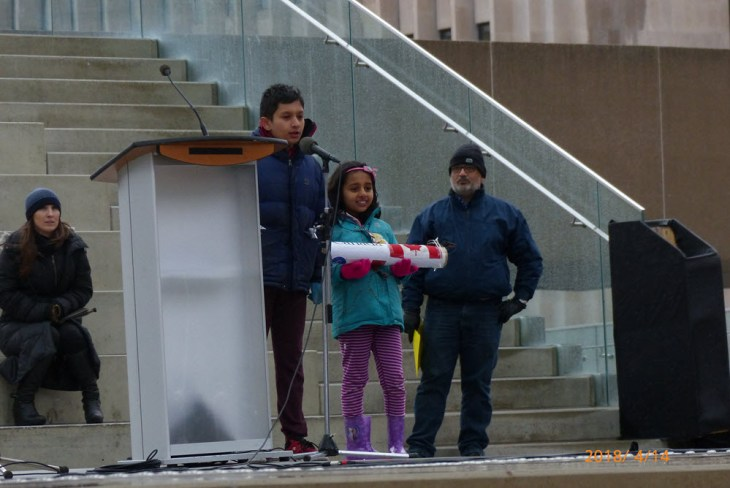 A boy and a younger girl standing next to an outdoor podium. An adult man and woman stand nearby.