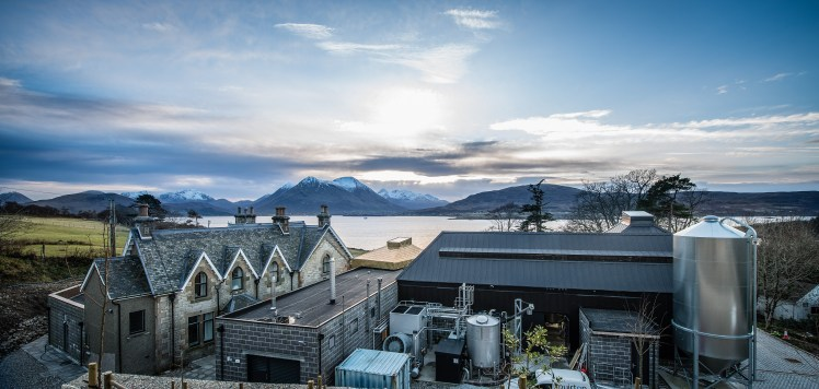 Raasay distillery from behind, overlooking the water and mountains in the background