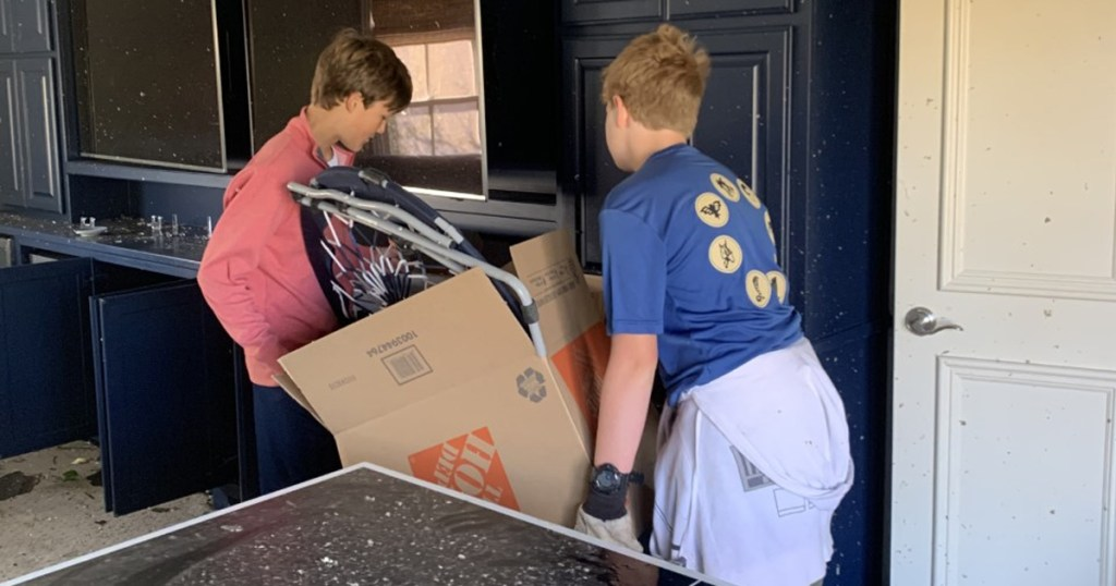 Slaton (left) and Oliver carry a box out of Slaton's house.