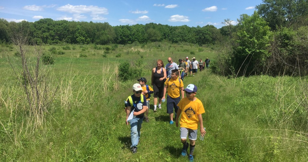 Pack 1855 Cub Scouts hike through a field