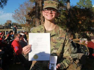 Shannon holds the Summit Award certificate and medal.