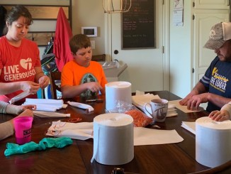 A family from Troop 599 works together to assemble face coverings