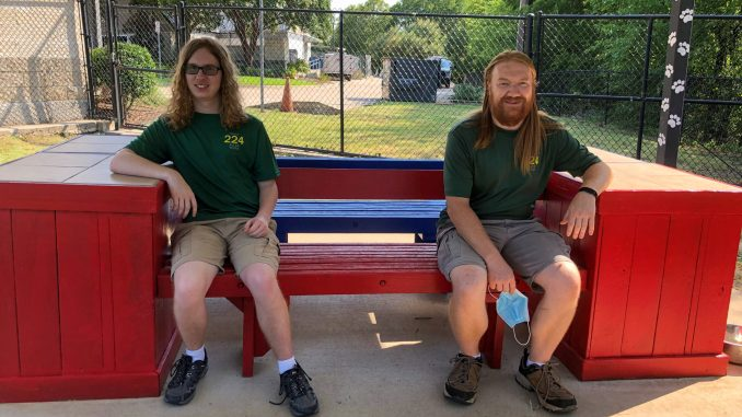 Ethan and Michael sit on benches.
