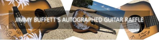 photo of autographed guitar laying on the beach