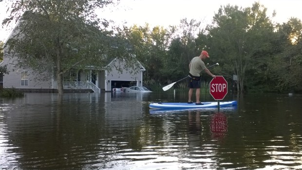 """Wilfred Baker rides his Sea Eagle Needlenose™ SUP through their neighborhood during a recent flood in Summerville, SC. """"A surreal experience,"""" says his wife, Wendy."""