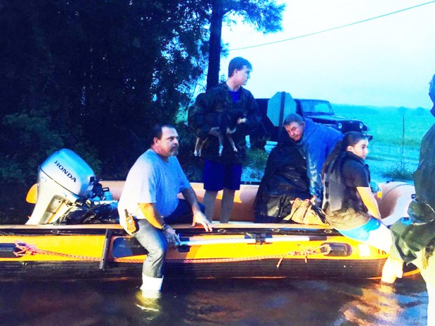 "Clay Stilley and his friends rescued about 100 neighbors who were stranded by deadly flooding. ""You can't see her well in the photo,"" said Clay, in grey t-shirt, ""But the photo was taken as we rescued a 90-year old woman. She's wrapped in a blanket at the bow of the Sea Eagle."""