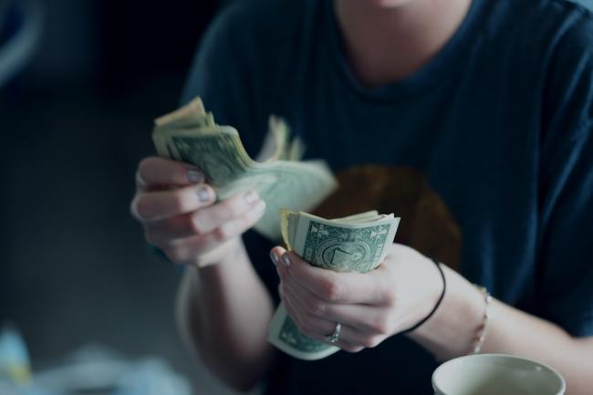 Na foto, uma mulher conta notas de dinheiro.