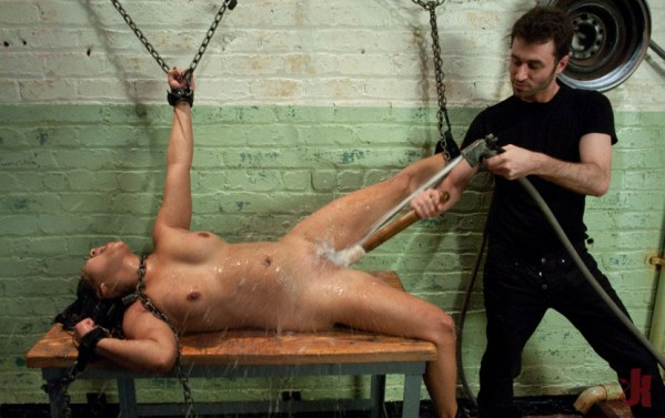 Chained whore gets her pussy stretched with dildo while being sprayed with a hose