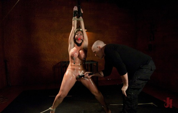 Busty, blonde slave is tied up has her nipples clamped and is forced to cum with a toy