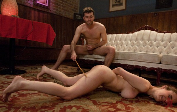 Master jerks off his cock while slave is on the floor tied up and beaten with a stick