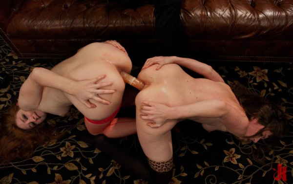 Two sluts in stockings share a double headed dildo on their knees in violent bondage
