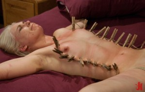 Submissive blonde gets her nipples and torso bound in nipple clamps while tied to a bed