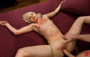 Submissive blonde gets her pussy fucked by a fat cock while being tied up to a huge bed