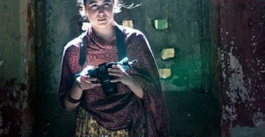 A still from the film The Ship of Theseus. A woman is standing in a room where some sunlight illuminates her face. She is holding a camera in her hands and is looking straight ahead.