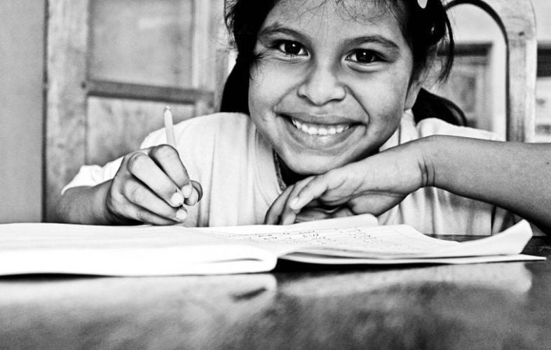 This is a close up photo of a girl student in a special needs classroom. A young girl is smiling into the camera while her chin is resting on the back of her right hand. In her left hand she is holding a pencil and there is a book in front of her.
