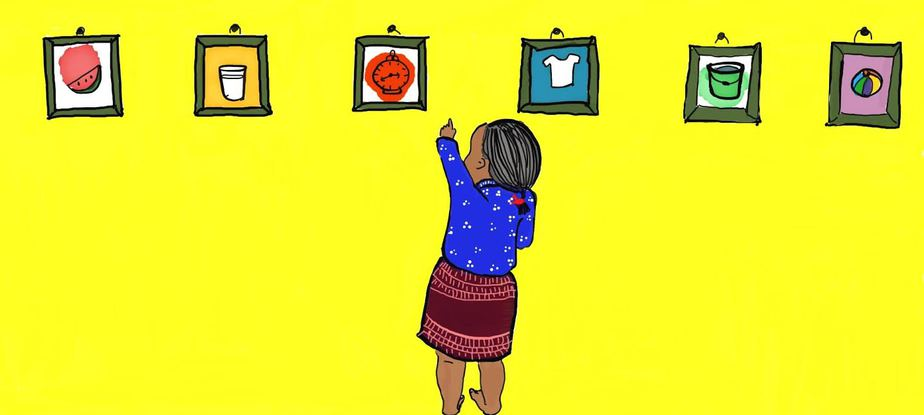 A little girl wearing a navy top and a purple skirt is reaching up and pointing at one painting in a series of paintings on a yellow wall.