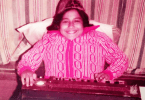 A picture of Abha as a child. She is wearing a pink and white sweater and is seated against striped curtains.
