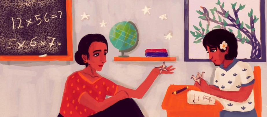 A teacher and child sit in a classroom, both holding pieces of origami. There is a blackboard on the wall with multiplication problems scribbled on it, and a shelf with a globe and some books on it. A leafy tree can be seen from the classroom window.