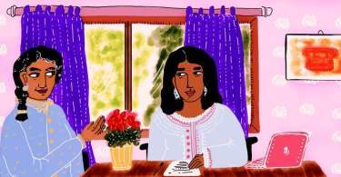 A person with a bindi on their forehead and a sheet of paper and laptop in front of them sits at a table. They are looking at the person beside them, who sits on a wheelchair and wears their black hair in a plait. A vase of red flowers is on the table between them and the walls are painted lavender.