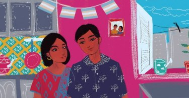 In a home, a couple stands smiling. One wears a dupatta and looks at the other, who wears a patterned shirt. On the bright pink wall behind them there is a photograph of the couple and a string of Transgender Pride Flags. In the background we see an open window and a kitchen.