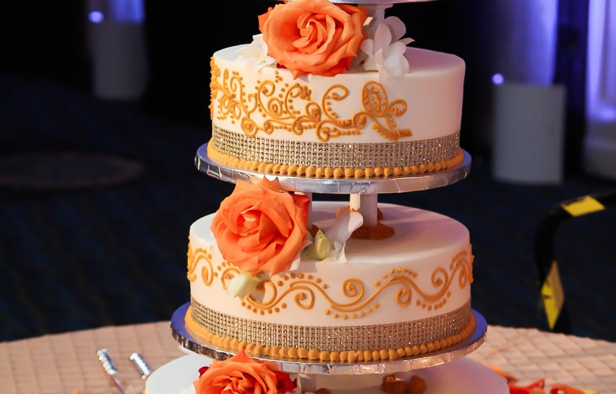 orange color 4 tier mehndi cake at an Indian wedding reception