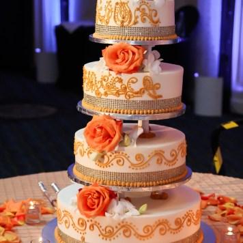 orange color 4 tier mehndi cake at an Indian wedding reception