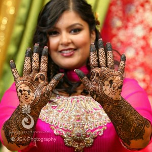 An Indian bride smiles for the camera, holding up her hands to show her mehndi