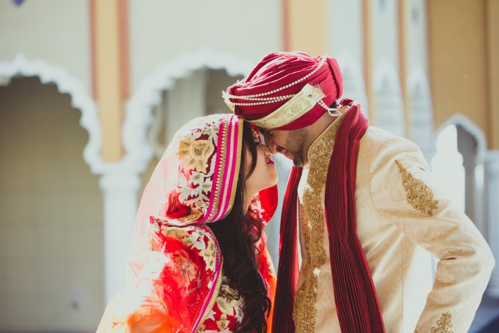 An Indian bride and groom making funny faces at each other at their wedding ceremony at the Gurdwara