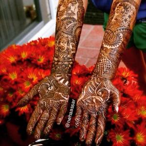 A bride's detailed mehndi design on her arms and hands