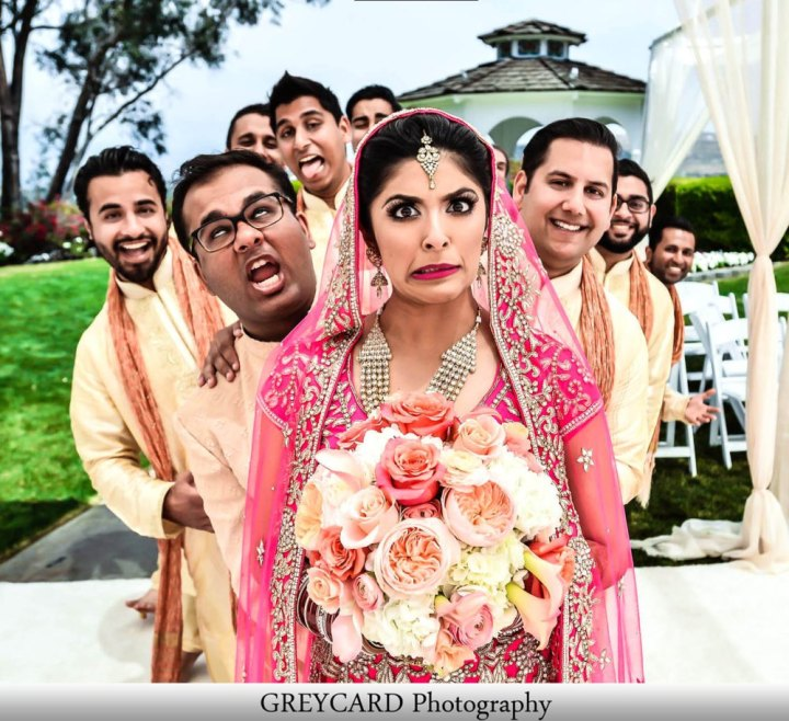 An Indian bride wearing a lehenga and the groomsmen behind her making funny faces into the camera at an Indian wedding.