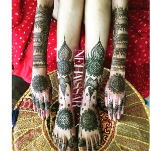 A bride's two arms and feet, showing off her intricte mehndi design by Neha Assar.
