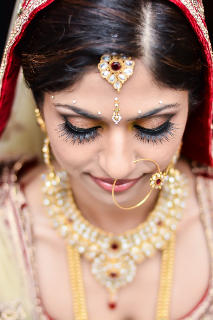 Indian bride's posing for a photo to show off her hair and makeup for her Indian wedding ceremony.