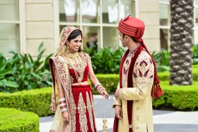An Indian bride and groom doing their first look photos dressed in their traditional ceremony clothes