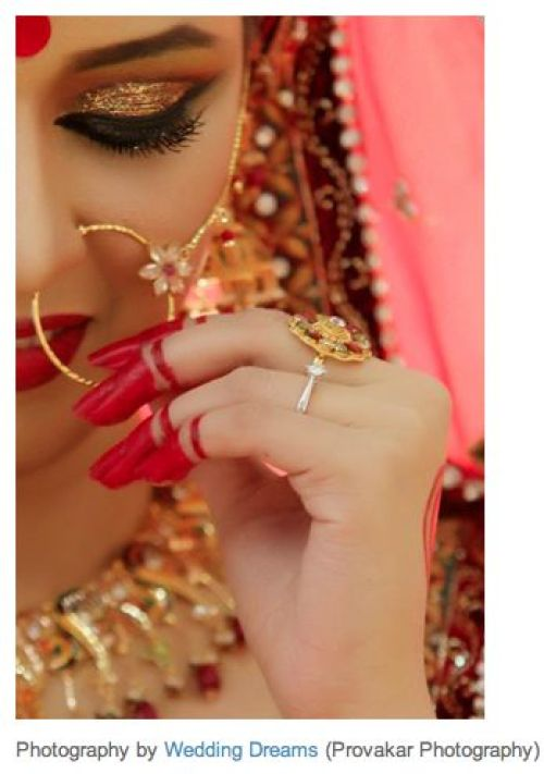 Indian wedding bride wearing nath. The mehndi on her hands enhances this photo. Her Indian wedding dress, lehenga, with her dupatta on her head gives her a classic dulhan - Indian bride look.