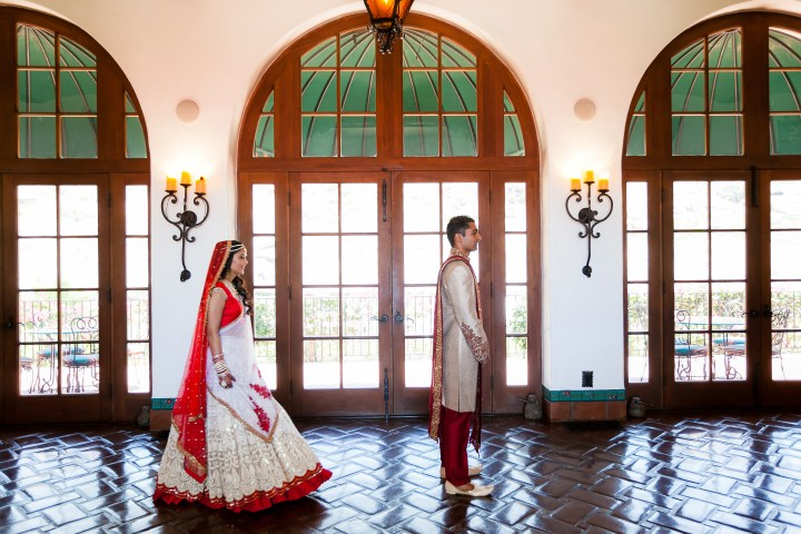 Indian bride wearing her lehenga going to meet her groom wearing his sherwani, for the first look before the ceremony started.