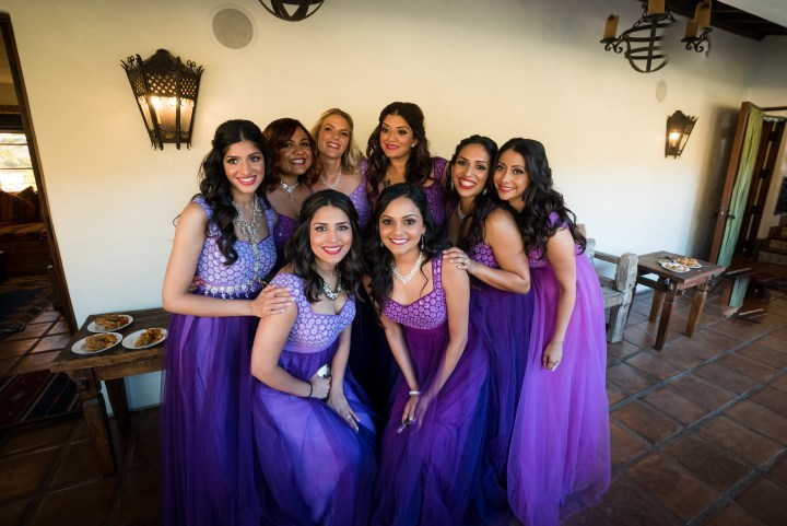 Bridesmaids wearing purple gowns at an Indian wedding reception.