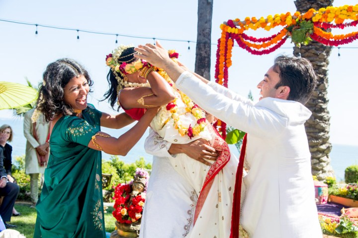 Indian bride and groom battling out the varmala at their Hindu wedding ceremony