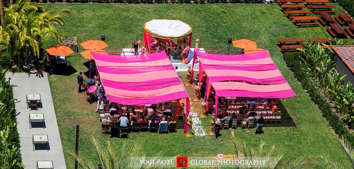 Indian weding outdoor ceremony with a pink canopy.