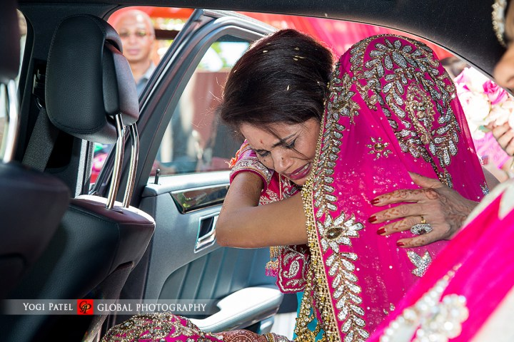 The bride wearing her pink lehenga at her vidai.