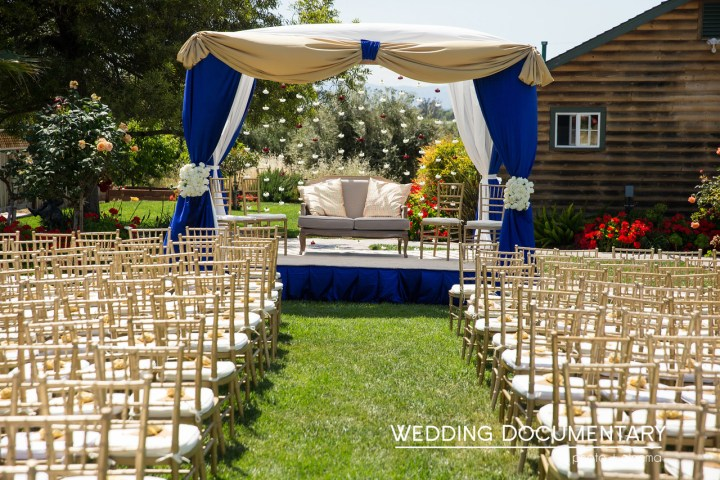 Gold chiavari chairs setup theater style in front of the mandap for an Indian wedding