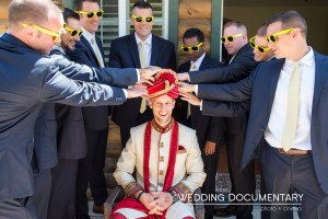 Groom dressed in a sherwani taking funny photos with his groomsmen.