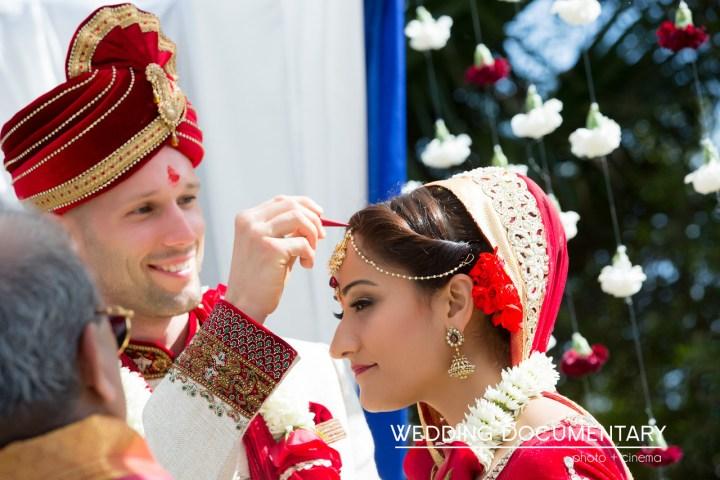 Groom wearing sherwani putting sindoor in bride's maang at Indian Hindu wedding ceremony.
