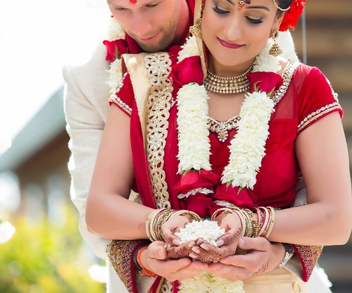 An Indian bride and her groom hugging before their Hindu wedding ceremony. starts.