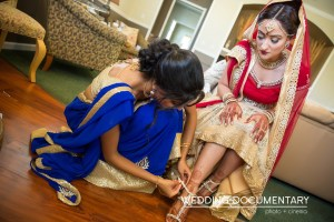 Indian bride wearing a lehenga getting help to get ready from one of her bridesmaids.