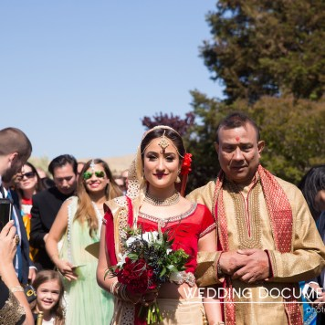 An Indian bride wearing a red and white lehenga escorted down the aisle by her father wearing a kurta.