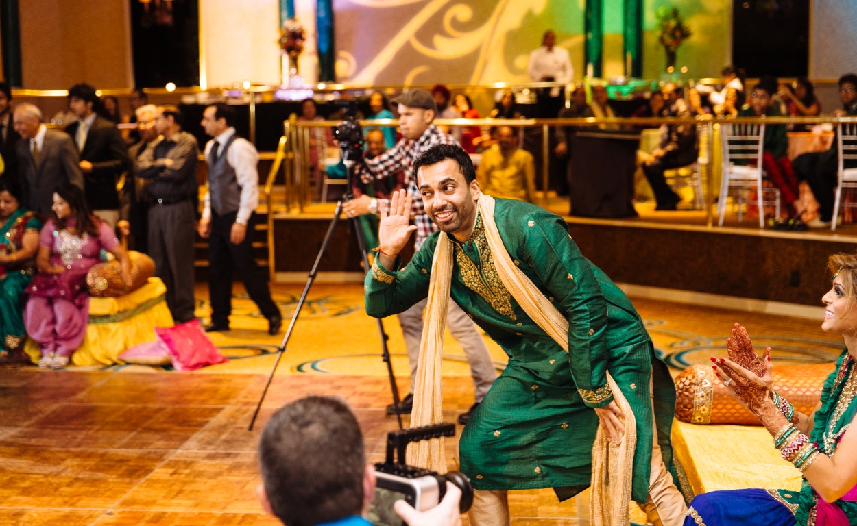 An Indian groom wearing his green kurta dancing at his sangeet.