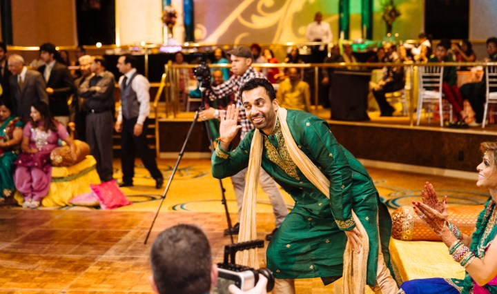 An Indian groom wearing his green kurta dancing at his sangeet.