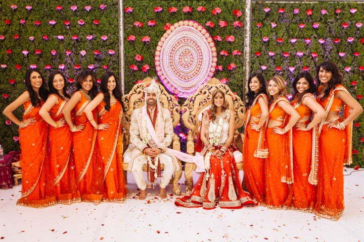 an Indian bride and groom sitting in their mandap posing for a photo with the bridesmaids.