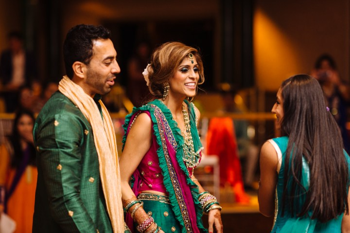 An Indian bride and groom mingling with guests at their wedding sangeet.