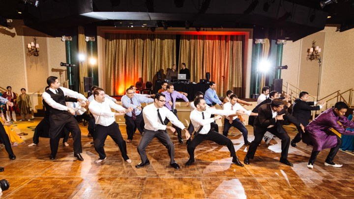 A group of guys doing a dance at an Indian wedding sangeet.